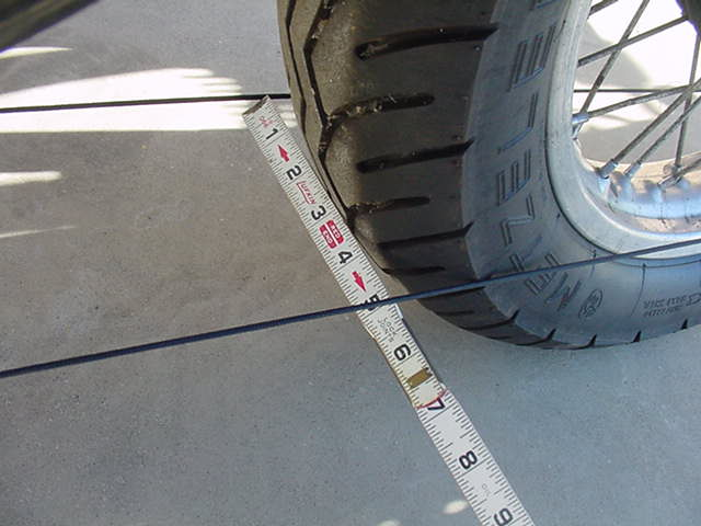 measure the distance between the strings this is the tire width now measure the strings just in front of the front tire the measurement must be the same